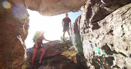 wspinaczka : Fit man helping woman climbing rock while the hiker couple is hiking together in adventurous nature Wideo