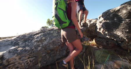 hiking : Hiking man helping his girl friend climbing a rock while traveling together in sunny outdoors Stock Footage