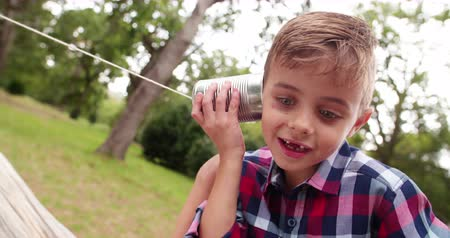toy : Cute little Boy curiously listening on tin can phone in park, concept for telephone or mobile communication. Stock Footage
