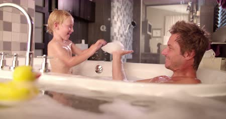 kád : Modern dad and son taking a bubble bath together and playing with soap suds at home in bathroom Stock mozgókép