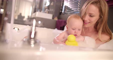 kisbaba : Modern Mom and infant daughter take bubble bath together playing with rubber ducky and covered in soap suds