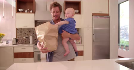 kitchen paper : Modern dad standing and holding infant daughter while unpacking groceries from paper back on counter, in sunlight filled kitchen.