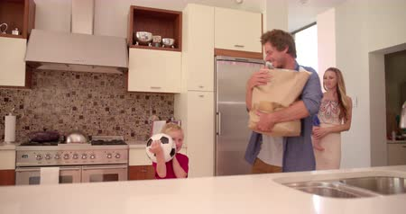 holding : Young Family with mother holding infant daughter and father unpacking groceries from paper bag onto the kitchen counter Stock Footage