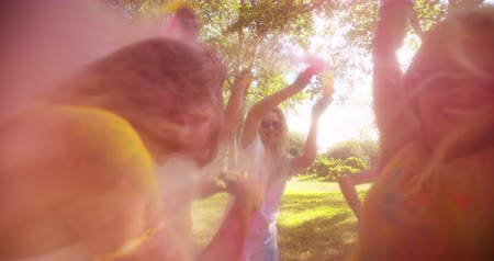 színek : Friends throwing Holi powder at each other at a Holi Festival in a park in the daytime