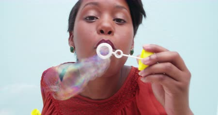 african decent : Silly african woman blowing soap bubbles, isolated on blue wall background