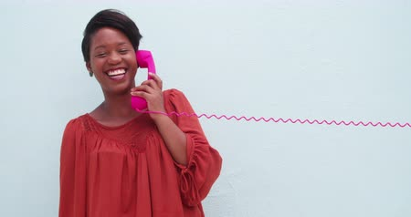 african decent : Beautiful young woman with a vintage telephone in retro style, isolated on blue wall background