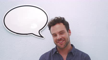 bas : Attractive man talking something, speech bubble above his head,  isolated on blue wall background