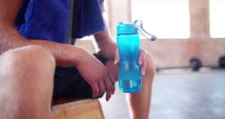 kurtarma : Young adult athletic man in sports clothing hydrating from a colored plastic water bottle at the gym during a crossfit training break
