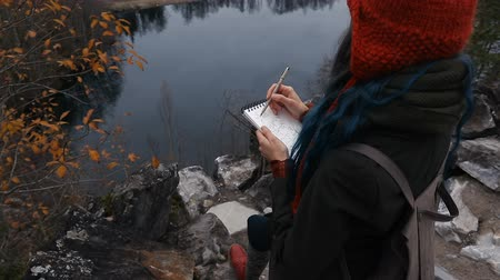artist girl painting sitting on the rocks at the cliff, notepad. Wonderful fall view