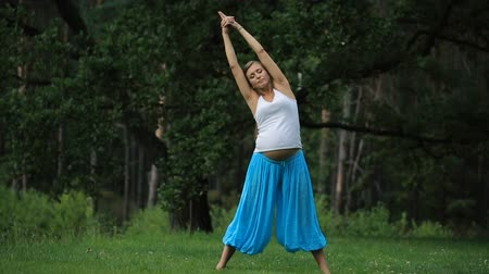 pregnant yoga prenatal maternity doing different exercises. in the park on the grass, breathing, stretching, statics.