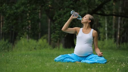 pregnant yoga woman drinking water from a bottle, in the lotus position. park ,grass ,.outdoor, forest.