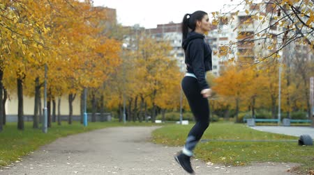 Woman feet jumping, using skipping rope in park. Wideo