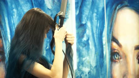 bodorítás : Pretty, young woman curling her hair in front of her bathroom mirror. Hair perm. Shower Curtains with Art painting.