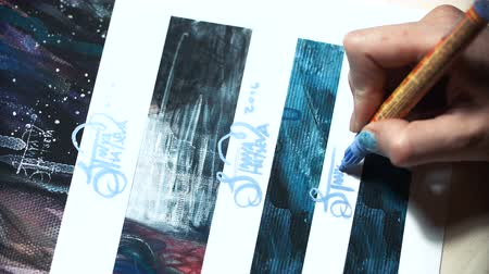 marker : Girl artist signs some of his works. Painted sign of a master. Signature print on a blue felt-tip marker Stock Footage