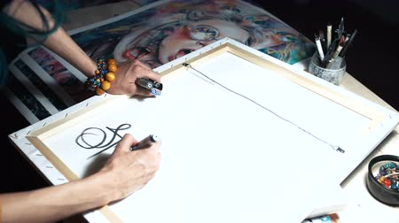 felvonás : Girl artist signs some of his works. Painted sign of a master. Canvas on a stretcher signature black marker.
