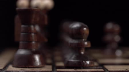 епископ : chess closeup, wooden chess board, business concept, black background. slide camera. Studio. Стоковые видеозаписи
