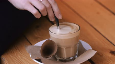 sweetened : Female hands add sugar refined sugar in a glass of cappuccino on a saucer and stir it.