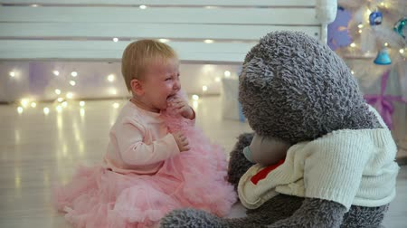 Пол : Little girl is crying with bear sitting on the floor