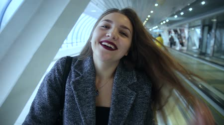 sentiment : Girl rides on travelators and smiling