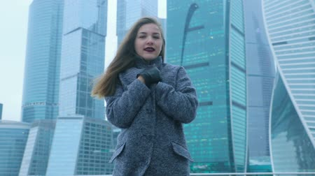 sightly : Girl posing against the backdrop of a skyscraper Stock Footage