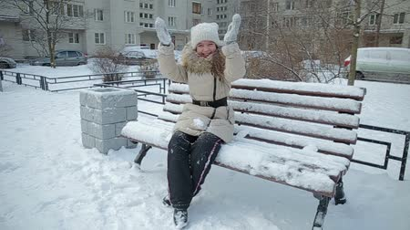 fur boots : Small girl on bench snowfall slow motion Stock Footage