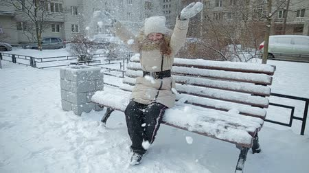 mittens : Small girl on bench snowfall slow motion Stock Footage
