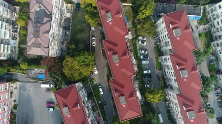 Aerial top down video showing roofs, lanes, cars and parking lots in an urban residential area