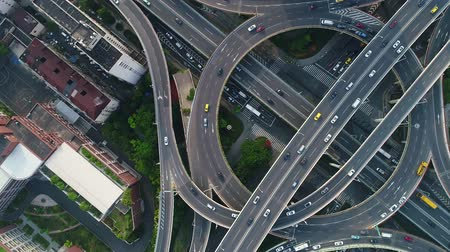 Rotating drone view into the center of busy multilevel interchange flyover in Shanghai showing afternoon traffic coming from the elevated roads. Stock mozgókép