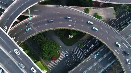 multiple lane : Rotating drone view into the center of busy multilevel interchange flyover in Shanghai showing afternoon traffic coming from the elevated roads