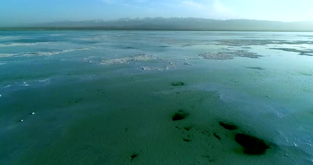 Flying drone over Chaka Salt Lake on the Tibetan Plateau showing the lake�s thick salt bed that lies close to the water surface, a blue cloudy sky and mountains in the background. Qinghai Province, China. Part 1 of 2