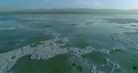 Flying drone over Chaka Salt Lake on the Tibetan Plateau showing the lake�s thick salt bed that lies close to the water surface, a blue cloudy sky and mountains in the background. Part 2 of 2