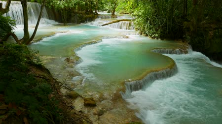 Turquoise natural swimming pools of the Kuang Si Falls, one of southeast Asia�s most beautiful water falls and a must visit around Luang Prabang. Stock mozgókép