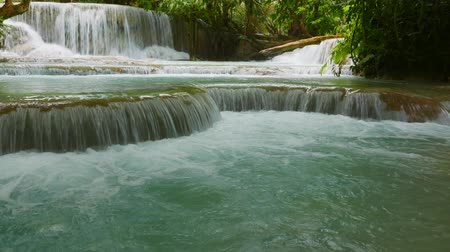Paradise-like rain forest landscape with one of southeast Asia�s most beautiful waterfalls, the Kuang Si falls with cascading natural swimming pools. Gimbel-stabilized 4k pan footage. Stock mozgókép