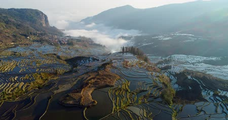 gerçeküstü : Drone flight over water-filled rice terraces towards a valley covered with dynamic mist. Yuanyang Rice Terraces early in the morning during spring. Part 1 of 4, can be merged to a continuous movie. Stok Video