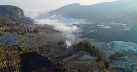 Drone flight over water-filled rice terraces towards a valley covered with dynamic mist. Yuanyang Rice Terraces early in the morning during spring. Part 2 of 4, can be merged to a continuous movie.