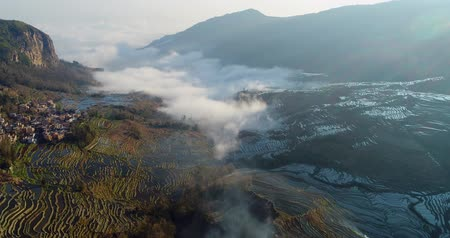 Drone flight over water-filled rice terraces towards a valley covered with dynamic mist. Yuanyang Rice Terraces early in the morning during spring. Part 3 of 4, can be merged to a continuous movie.