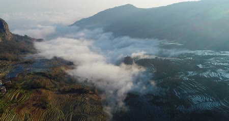 Drone flight over water-filled rice terraces towards a valley covered with dynamic mist. Yuanyang Rice Terraces early in the morning during spring. Part 4 of 4, can be merged to a continuous movie. Stock mozgókép