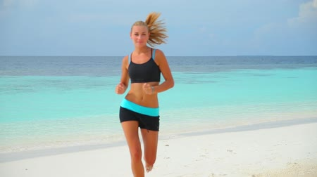 estilo de vida saudável : Woman running on the beach, beautiful sportive female doing exercise outdoors, healthy lifestyle, active summer vacation. Full HD Video 1920x1080