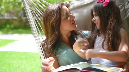 quintal : Beautiful mother with daughter reading book on backyard, sitting in hammock and talking with pleasure, enjoying happy family life.Full HD Video 1920x1080 Vídeos