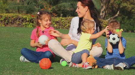 três : Happy family having fun outdoors, beautiful young mother with her three adorable kids sitting on fresh green grass field in the park and playing games. Full HD Video 1920x1080