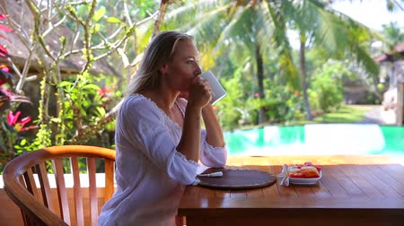 távozás : Pretty woman drinking tea, sitting on the terrace on the tropical beach resort and enjoying fruits and tea for breakfast in the morning, exotic summer vacation. Full HD Video 1920x1080