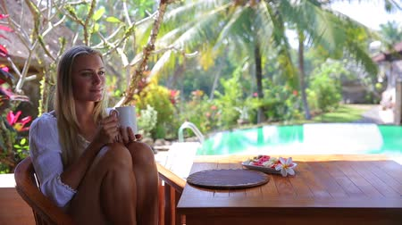 holiday villa : Pretty woman drinking tea, sitting on the porch of a tropical beach villa, enjoying fruits and tea for breakfast in the morning, exotic summer vacation. Full HD Video 1920x1080
