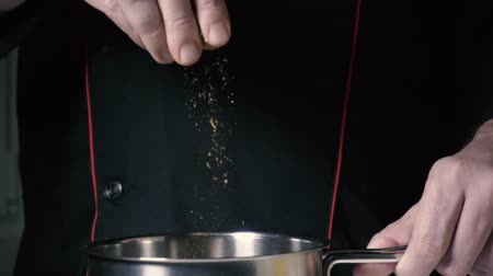 sůl : Slow mo chef throws a pinch seasoning in a metal pan
