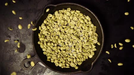 vagens : Raw green coffee beans fall down on the pan slow mo