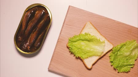 sprats : Sandwich with sardines, sprats on white toast, on the board, prepared and eaten, top view. Stop motion, animation