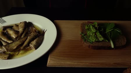sprats : Chef cook in a black jacket makes a sandwich on a black bread with sprats and lettuce, on a blackboard on a black table Stock Footage