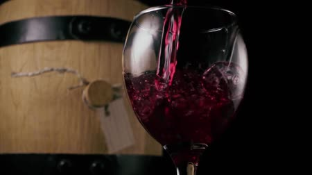 wine red : Red wine is poured into a wineglass against the background of a wine barrel. Black background. Slow motion