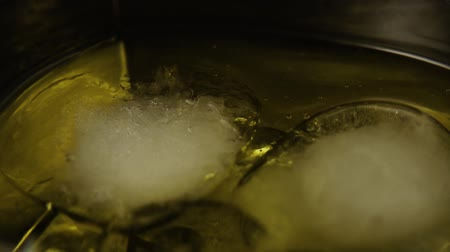viski : Slow motion. Ice cubes in an alcoholic drink swim counter-clockwise to the left close-up