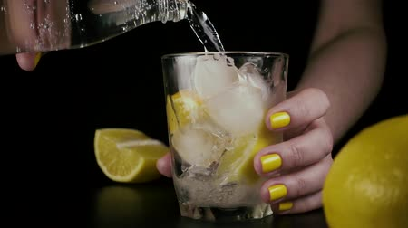 ginástico : Female hands from a glass bottle pour soda water into a glass with ice and lemon. Slow mo