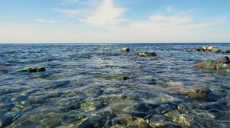 Slow mo a blue sky and a clear blue sea with a stony shore and rocks in the water Stok Video